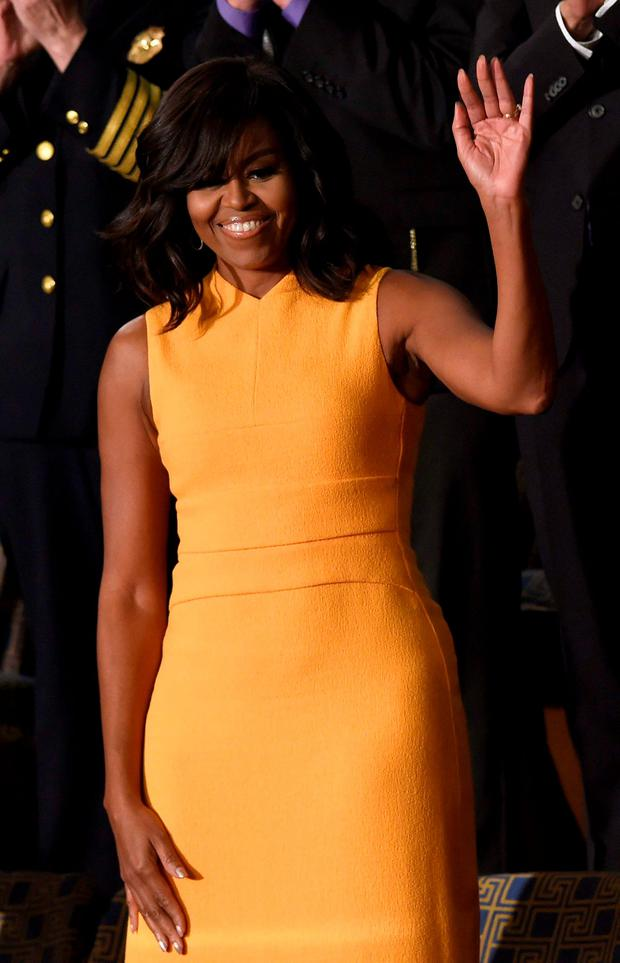 US First Lady Michelle Obama (C) waves before the arrival of US President Barack Obama before the State of the Union Address during a Joint Session of Congress at the US Capitol in Washington, DC