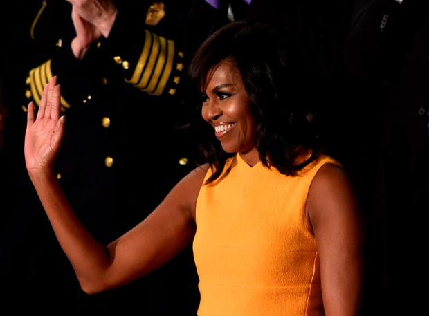 US First Lady Michelle Obama waves before the arrival of US President Barack Obama before the State of the Union Address during a Joint Session of Congress at the US Capitol in Washington, DC