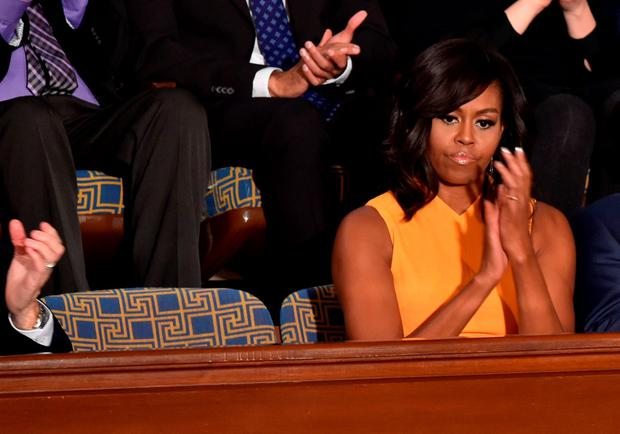 US First Lady Michelle Obama sits beside an empty chair (L) as her husband US President Barack Obama delivers his State of the Union address before a Joint Session of Congress at the US Capitol