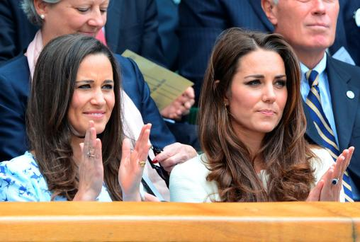 Catherine, Duchess of Cambridge and her sister Pippa Middleton (L) watch from the Royal Box before the men's singles final match between Britain's Andy Murray and Switzerland's Roger Federer on Centre Court on day 13 of the 2012 Wimbledon Championships