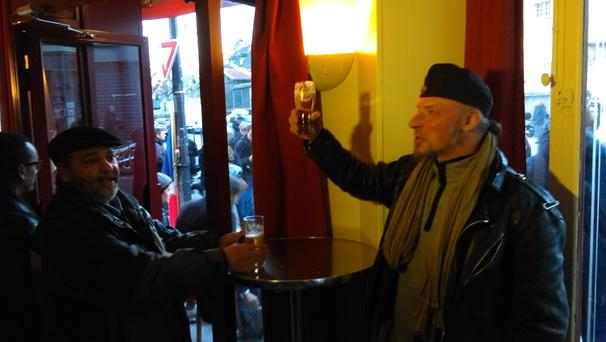 A customer raises his glass in a toast to freedom in Le Carillon which reopened today, two months after the Nov 13 attacks in which dozens were murdered. Photo: Shane Fitzsimons
