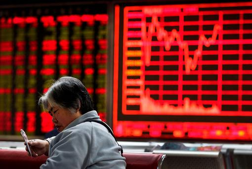 A woman plays cards with other investors at a brokerage house in Beijing. Photo: AP