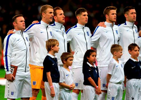 England captain Wayne Rooney (left) sings the national anthem with his team-mates before an international friendly match. Photo: PA
