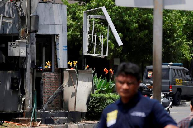 Indonesia Police make line near one of location bomb in Jakarta, Indonesia, Thursday, Jan. 14, 2016