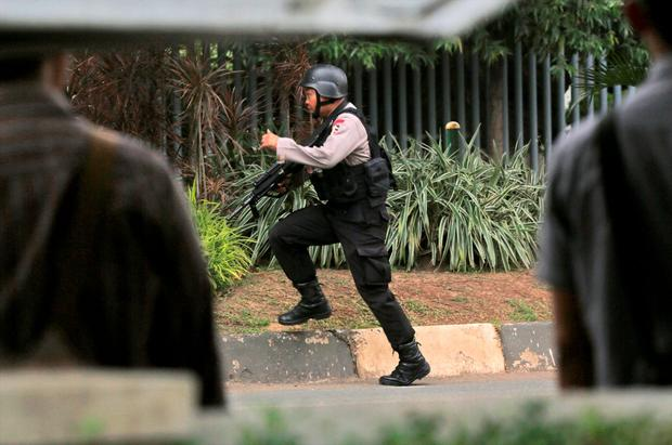 A police officer takes his position near the site where an explosion went off in Jakarta, Indonesia Thursday, Jan. 14, 2016