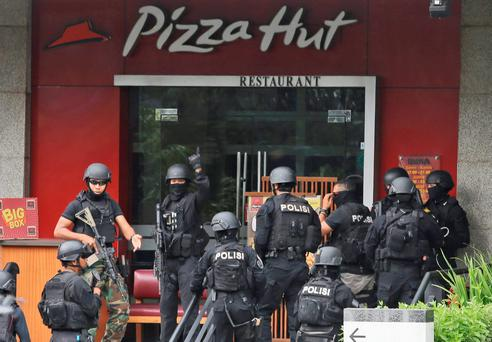 Police officers gather outside a Pizza Hut restaurant next door to a Starbucks cafe which was attacked in Jakarta