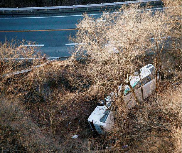 A bus lies after it veered off to the opposite lane on a mountain road in Karuizawa, Nagano prefecture, central Japan Friday, Jan. 15, 2016. Rescue officials say the overnight tour bus on its way to a ski resort in central Japan slid down the mountainside, killing at least more than a dozen passengers.