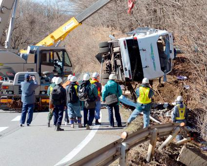 A damaged bus is lifted by crane on a mountain road in Karuizawa, Nagano prefecture, central Japan Friday, Jan. 15, 2016.