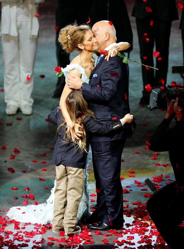 Singer Celine Dion is embraced by her husband and manager Rene Angelil and their son Rene-Charles Angelil after the final performance of her show