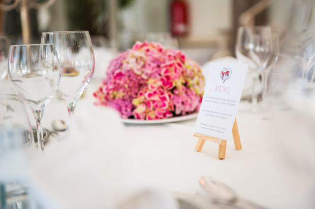 Table with wine glasses, menu and flower arrangement at wedding reception