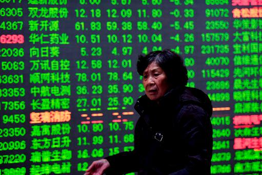 An investor at a brokerage house in Hangzhou, Zhejiang Province, China. China stocks, which show green when falling, dropped more than three percent on Friday alone. Photo: Reuters/Stringer.