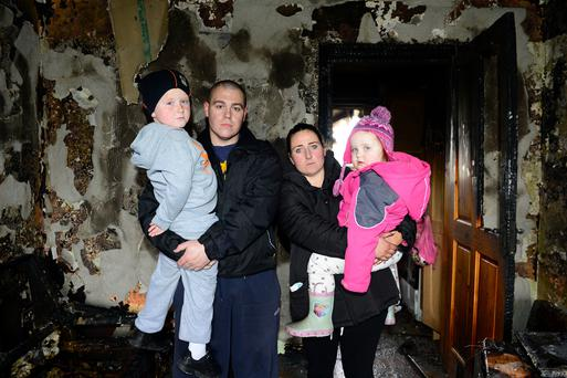 Vincent and Catherine Devine are pictured with their children Vincent junior (6) and Joyce (3) in their Ballsgrove home which was completely destroyed. Picture: Ciara Wilkinson.
