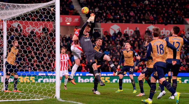 Arsenal's Czech goalkeeper Petr Cech (C) jumps to make a save during the English Premier League football match between Stoke City and Arsenal at the Britannia Stadium