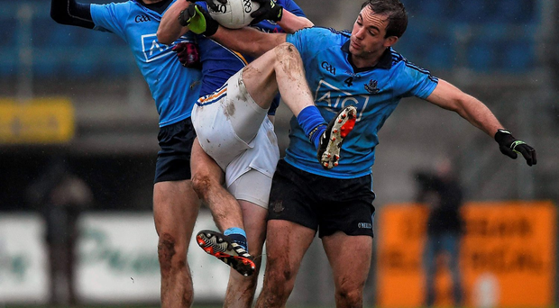 Darren Gallagher of Longford holds onto the ball under pressure from Dublin pair Niall Scully (L) and Tomás Brady.. Picture credit: Ray McManus / Sportsfile