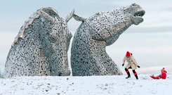A mother and a child sledging at the Kelpies in Falkirk, Scotland. Photo: Andrew Milligan/PA Wire