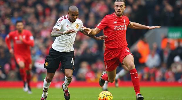Ashley Young challenges for the ball with Liverpool captain Jordan Henderson