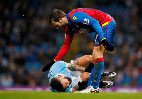 Manchester City's Nicolas Otamendi lies injured as Crystal Palace's Yohan Cabaye looks over.