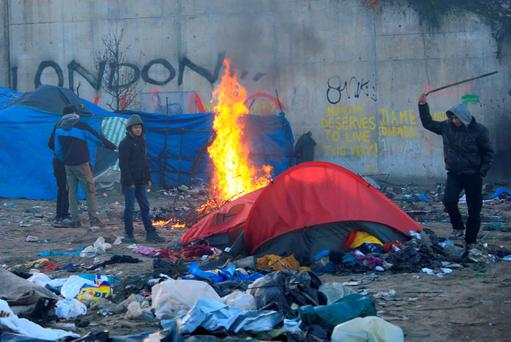 A migrant hits a former shelter with a stick in a dismantled area of the camp known as the