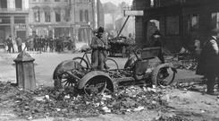 A burned-out car which had been used as a barricade lies in a Dublin street in the aftermath of the 1916 Rising. Sinn Féin is seeking to link events in 1916 to the Provos' 30-year campaign of violence Photo: Topical Press Agency/Getty Images