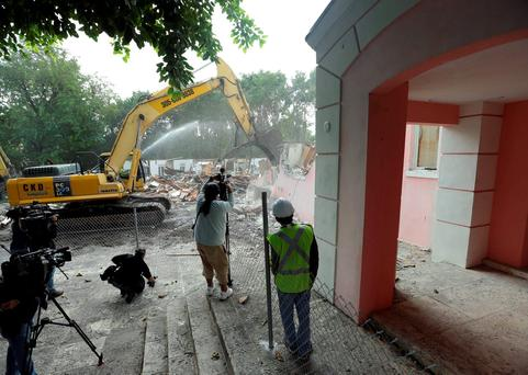 An excavator demolishes the waterfront mansion formerly owned by Colombian drug lord Pablo Escobar, Tuesday, Jan. 19, 2016, in Miami Beach, Fla. Chicken Kitchen owner Christian de Berdouare, who purchased the property in 2014, wants to build a more modern home on the site