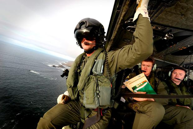 Sgt Mark Dunne ensures a clear final approach while Lt Col Verling Donnagh holds the proclamation and national flag with airman Stephen Gleeson (right) before they deliver the Proclamation and the national flag to schools off the northwest Donegal island of Arranmore. Picture; GERRY MOONEY