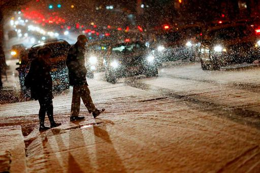 People cross a street as it snows in Washington, January 20, 2016. Icy roads and freezing temperatures prompted school closings and emergency preparations in several states in the U.S. South on Wednesday, as snow began to fall on some areas ahead of a major storm expected to blast snow across the Northeast later this week