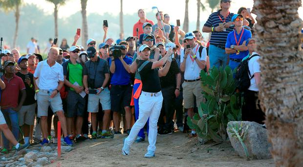 Rory McIlroy of Northern Ireland plays his third shot at the par 4,9th hole after taking a penalty drop after his drive had finished in the water hazard during the second round of the 2016 Abu Dhabi HSBC Golf Championship at the Abu Dhabi Golf Club