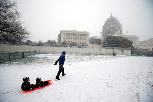 Ben Cichy pulls a sled with his sons Adrian, 18-months-old, and Logan 3, inside as they head for sledding in the snow on Capitol Hill, Friday, Jan. 22, 2016 in Washington Photo: AP