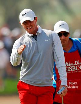 Ireland's Rory McIlroy shares a joke with his caddie at the 18th hole during the second round