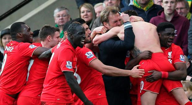 Adam Lallana celebrates with team mates and manager Juergen Klopp after scoring the fifth goal for Liverpool