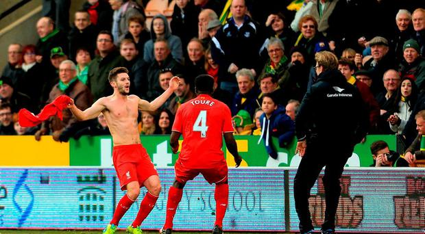Adam Lallana celebrates scoring his team's fifth goal with his manager Jurgen Klopp (R) and team mate Kolo Toure