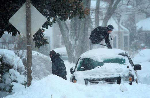 Residents clear snow from their car during a heavy snow fall. (Photo by Win McNamee/Getty Images)
