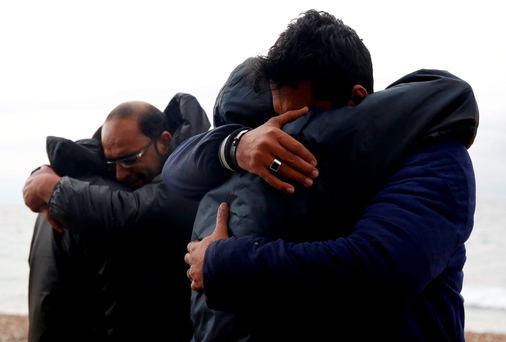 On dry land: Iraqi refugees hug following their arrival on an inflatable raft on the Greek island of Lesbos. Photo: REUTERS/Giorgos Moutafis