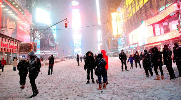 Pedestrians walk through the snowy streets near Times Square as all cars but emergency vehicles are banned from driving on the road (Photo by Yana Paskova/Getty Images)