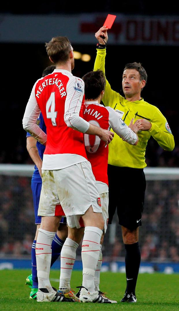 Referee Mark Clattenburg (R) shows a red card to Arsenal's German defender Per Mertesacker