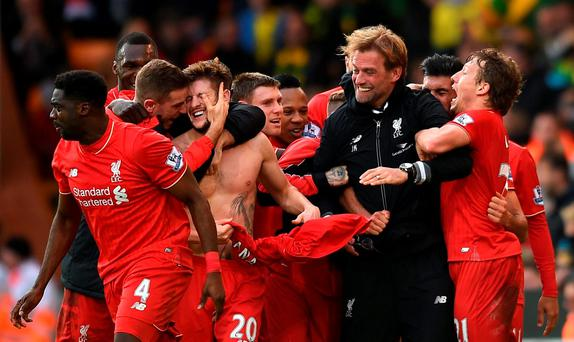 Liverpool's Adam Lallana (20) celebrates with his team-mates and manager Jurgen Klopp after scoring his side's fifth goal during the match against Norwich. Photo: Jon Buckle/PA Wire.