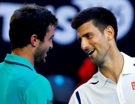 Novak Djokovic, right, shakes hands with Gilles Simon of France after winning their fourth round match at the Australian Open tennis championships in Melbourne. Photo: Vincent Thian/AP