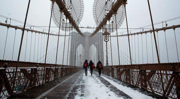 People walk across the Brooklyn Bridge during a snowstorm in the Manhattan borough of New York January 23, 2016