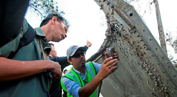 A Malaysian official (C) takes pictures of a piece of suspected aircraft debris after it was found by fishermen on January 23, at a beach in the southern province of Nakhon Si Thammarat on January 25, 2016