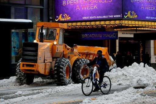 A delivery person on a bicycle passes a front end loader working to remove snow in Times Square in New York. Photo: Reuters