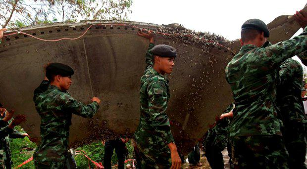 Thai soldiers carry a piece of suspected aircraft debris after it was found by fishermen on January 23, at a beach in the southern province of Nakhon Si Thammarat on January 25, 2016.