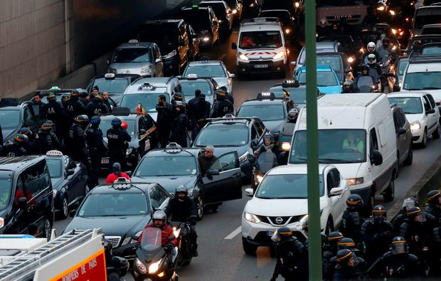 Anti-riot policemen arrive as taxi drivers block the traffic during a demonstration against the VTC (transport vehicle with chauffeur) on January 26, 2016 on the ringroad (peripherique) at porte Maillot in Paris