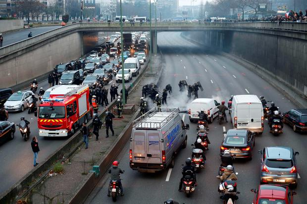 Anti-riot policemen take away a barrier during a taxi drivers demonstration against the VTC (transport vehicle with chauffeur) on January 26, 2016 on the ringroad (peripherique) at porte Maillot in Paris