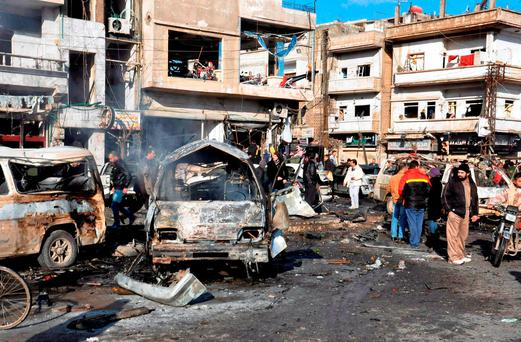 Syrian citizens gather at the scene where twin bombs exploded at a government-run security checkpoint, at the neighborhood of Zahraa, in Homs province, Syria. (SANA via AP)