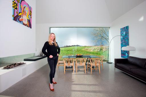 Entrepreneur Louise McGuane in the dining room, which has a 32ft-high ceiling and a massive expanse of glass, affording stunning views of the countryside and sky. Photo: Tony Gavin.