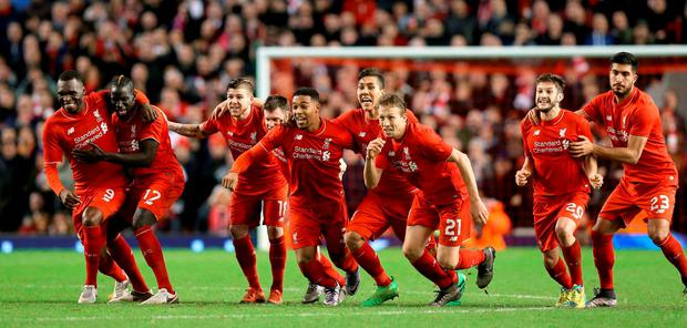 Liverpool players celebrate winning the penalty shootout during the Capital One Cup, semi final, second leg at Anfield
