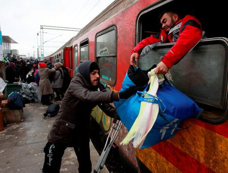 Refugees disembark from a train as they arrive to the transit centre for refugees near northern Macedonian village of Tabanovce (AP Photo/Boris Grdanoski)