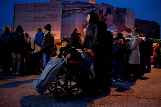 A Syrian woman carry her child on a wheelchair after they disembarked from a Ferry at the Athens' main port of Piraeus, early Wednesday, Jan 27, 2016. (AP Photo/Petros Giannakouris)