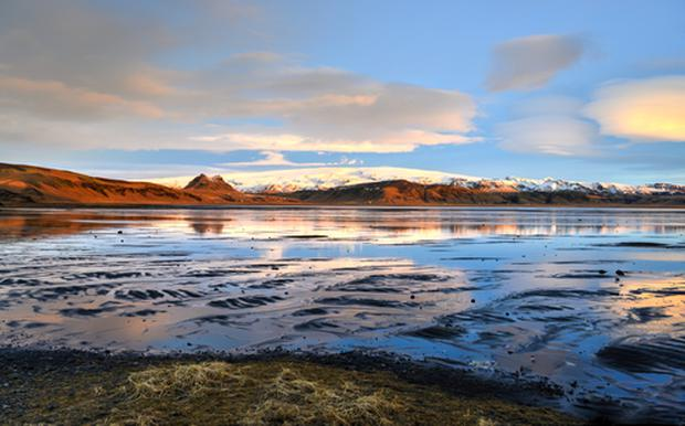 Approach to Dyrholaey at sunrise, Southern Iceland with Myrdalsjokull Glacier in the background.