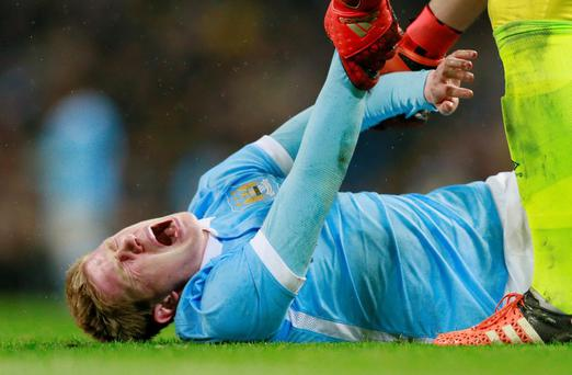 Manchester City's Kevin De Bruyne reacts after sustaining an injury as Everton's Joel Robles helps him during the Capital One Cup semi-final
